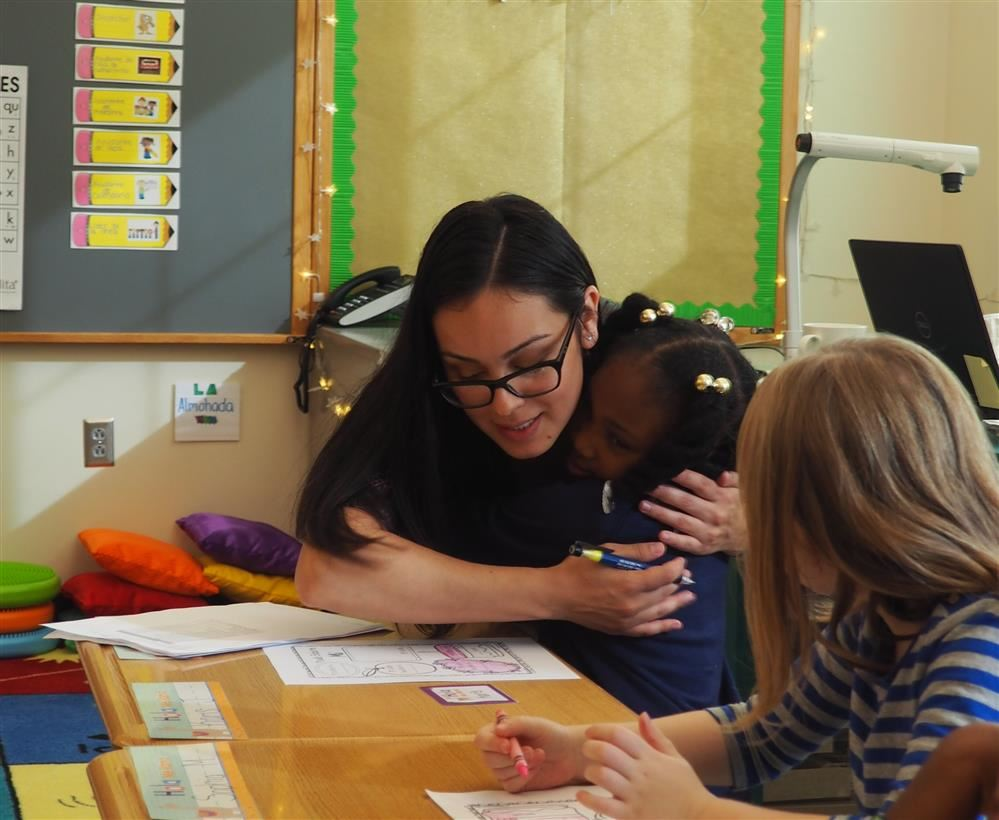 teacher hugging a child while working at the child's desk