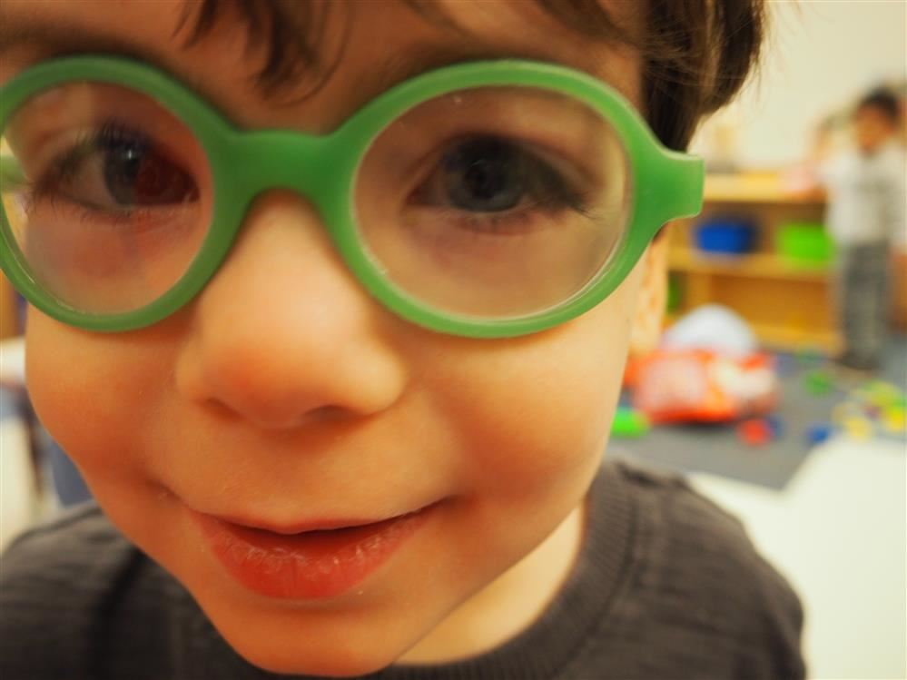 Close up of kid with green glasses